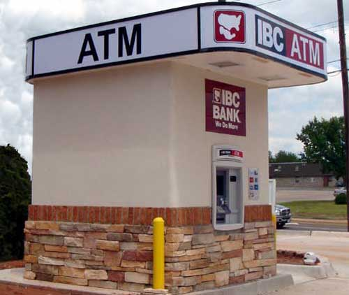 Photo of an ATM installed as a standalone kiosk with stucco walls