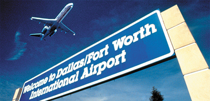 Picture of Dallas / Ft. Worth airport sign with airplane in background, nearby Dallas Warehouse